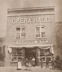 A few people stand in front of the C. Harding & Co. General Store on a summer day about 1890.  The words 'Opera Hall' appear in large letters above the second-floor windows. - , Utah