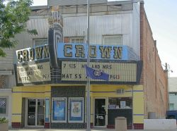 The marquee of the theater has a crown in the middle with the name 'Crown' on either side.  Below the marquee are two poster cases, with exit doors on the left and an entrance door on the right. - , Utah